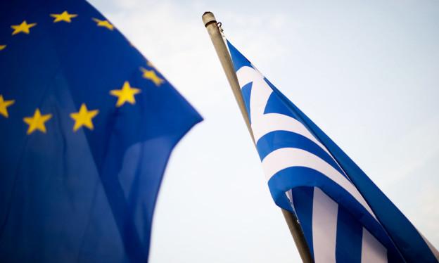 Links die EU-Flagge, rechts die griechische, vor blauem Himmel wehend.