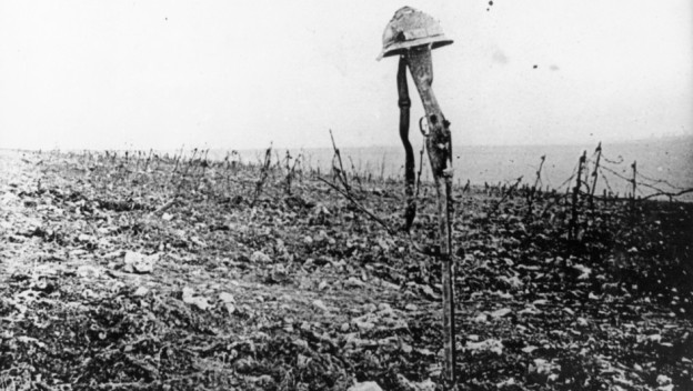 Schwarz-weisse Aufnahme eines Schlachtfeldes mit im Boden steckendem Gewehr und Helm darauf.