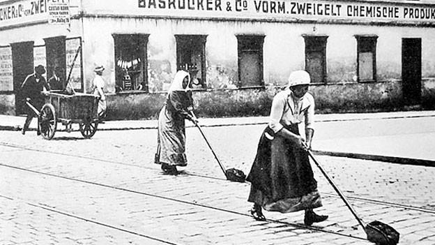 Frauen reinigen Tramschienen.