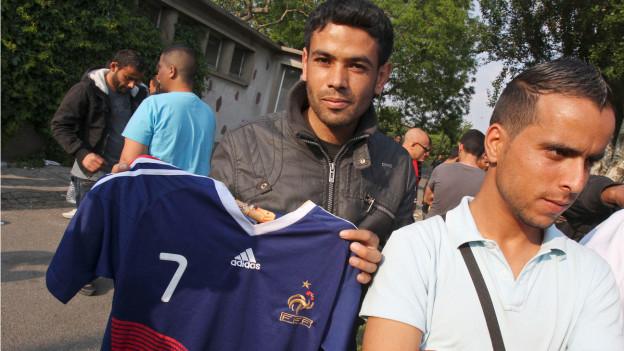 Ein Tunesier hält ein französisches Fussballdress.