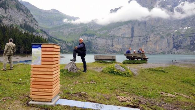 Ein paar Menschen stehen an einem Bergsee, davor steht eine quadratische Holzskulptur.