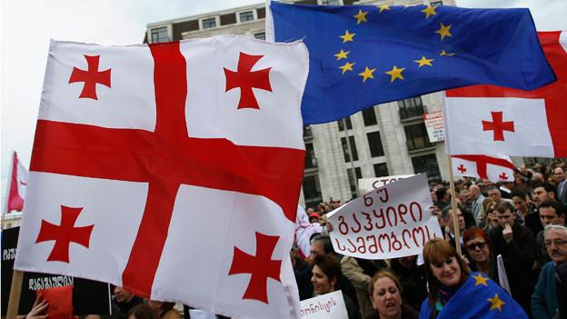 An einer Demonstration halten Menschen georgische und EU-Flaggen in die Luft.