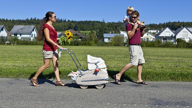 Junge Eltern mit zwei Kindern beim Spazieren