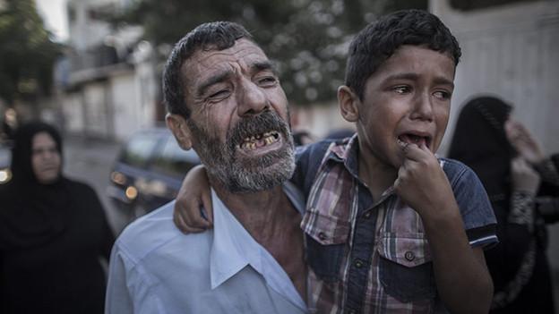 Ein Mann hält einen Jungen, beide weinen.