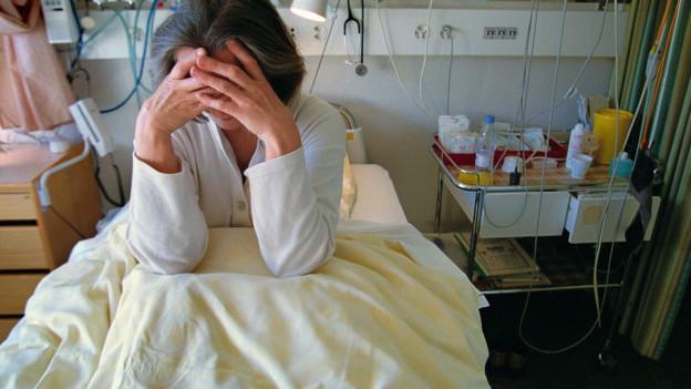 Frau sitzt verzweifelt in Spitalbett.