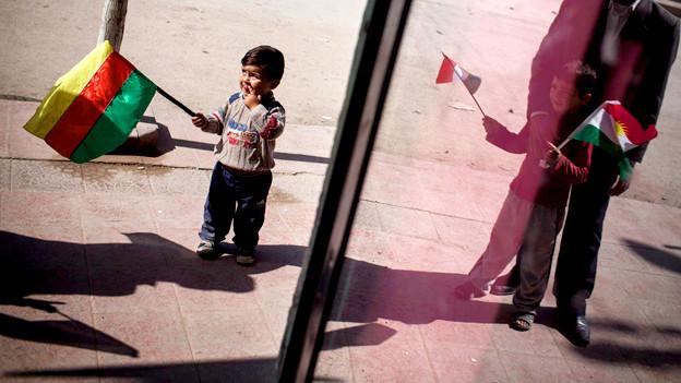Kleine kurdische Jungen mit der kurdischen Flagge.
