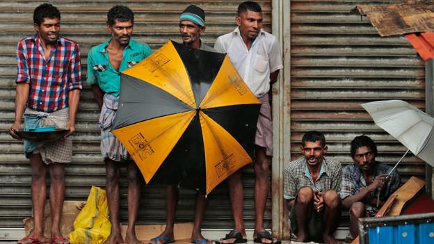 Männer stehen vor einem geschlossenen Geschäft.