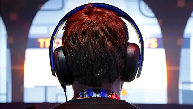 Ein Mann mit Kopfhörern spielt ein Computerspiel