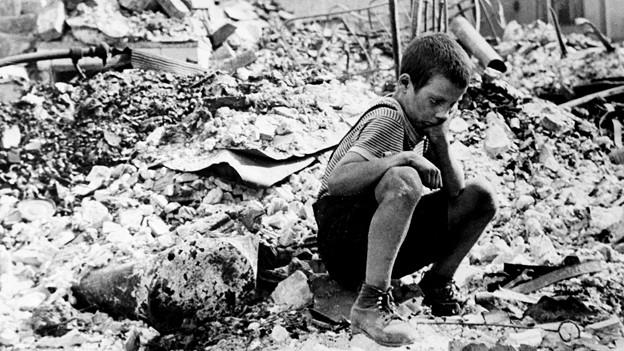 Junge kniet auf Trümmerfeld.