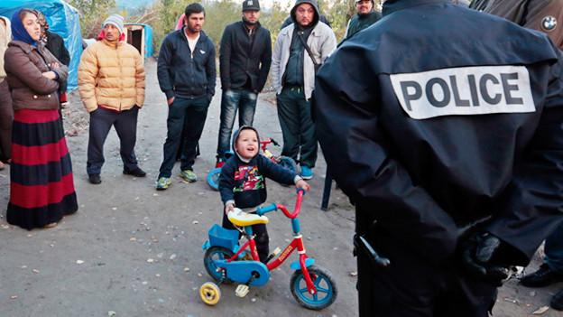 Ein Roma-Kind stellt sich schützend zwischen Polizeibeamte und seine Familie als diese vertrieben wird.