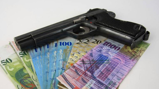 Pistole liegt auf Schweizer Banknoten.