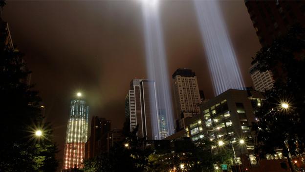 Der Freedom-Tower in den Farben der amerikanischen Flagge im Hintergrund, im Vordergrund die World Trade Center-Tribute Lichtsäulen.