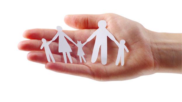 Ein Scherenschritt, der eine Familie darstellt, liegt auf einer Hand.