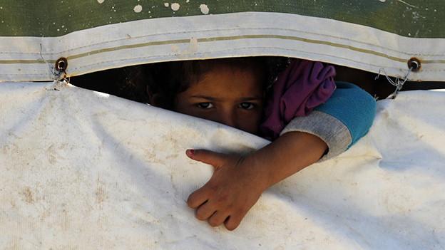 Ein Mädchen blickt durch einen Spalt zwischen zwei Tüchern