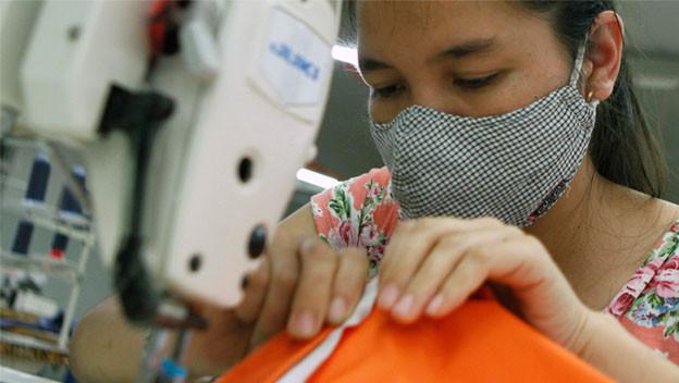 Textilarbeiterin arbeitet an einer Nähmaschine.