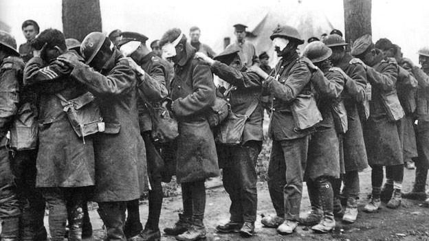 Soldaten mit zugedeckten Augen stehen in einer Schlange und halten sich an den Schultern.