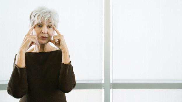 Eine Frau mit grauem Haar hält sich die Finger an die Stirn.