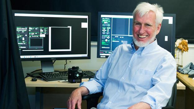 O'Keefe sitzt lachend in seinem Büro.