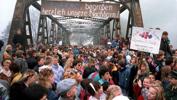 Leute begrüssen DDR-Bürger im Westen.