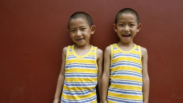 Zwei lachende Knaben in identischer Kleidung.