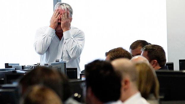 Ein Mann hält in einem Grossraumbüro entsetzt die Hände vors Gesicht.