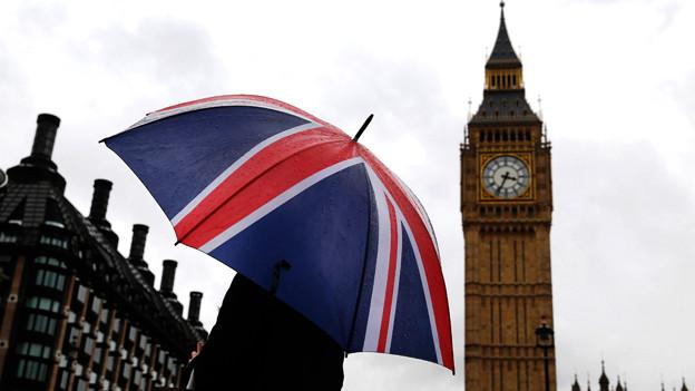 Eine Person mit einem Schirm mit der Grossbritannien-Flagge steht vor dem Big Ben.