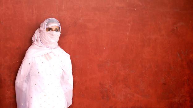 Eine weiss verschleierte junge Frau vor braunroter Wand.