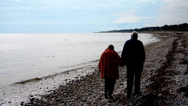 Ein älteres Paar geht dem Meer entlang.