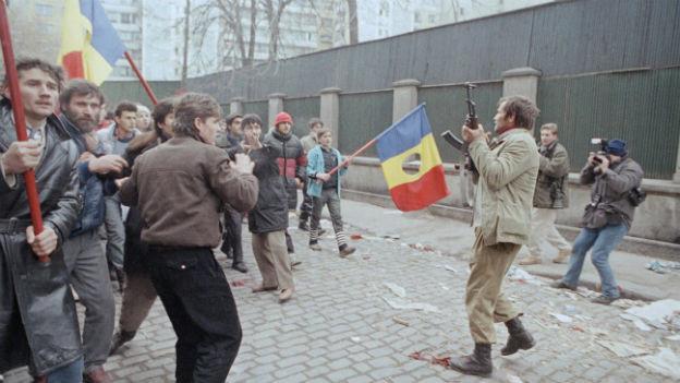 Aufständische gehe in Rumänien auf die Strasse. Sie tragen die rumänische Flagge.