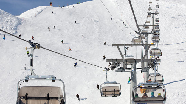 Skipiste mit vielen Skifahrern, im Vordergrund ein Sessellift