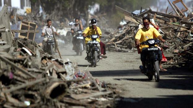Eine von Trümmern gesäumte Strasse, auf der Männer mit Rollern fahren.