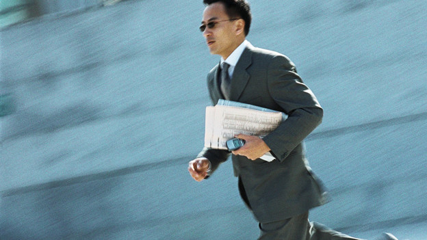 Ein Mann mit Sonnenbrille und Anzug rennt durchs Bild