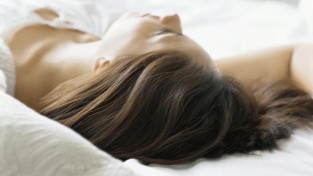 Eine Frau schläft in einem Bett mit weisser Bettwäsche.