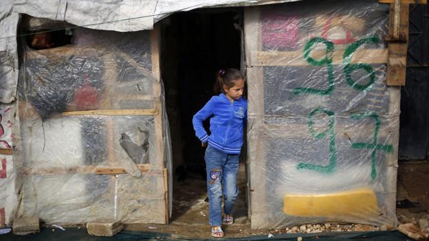 Ein Mädchen steht vor einer Holzhütte