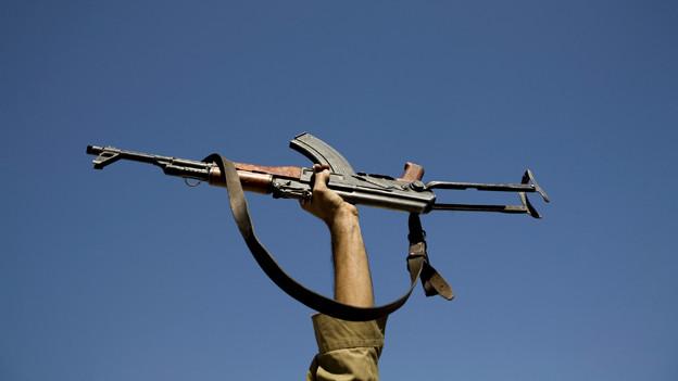 Eine Hand hält ein Maschinengewehr in die Luft