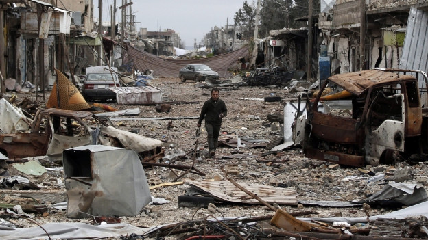 Ein Mensch geht durch das bombartie Kobani.