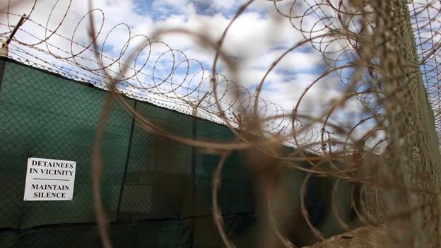 Bild vom Stacheldraht, der Guantànamo umzäunt, überfangen von einem wolkendurchzogenen Himmel.