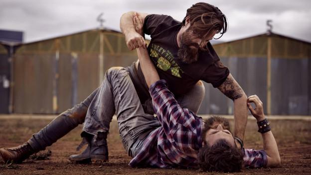 Zwei kämpfede Männer rangeln sich am Boden.