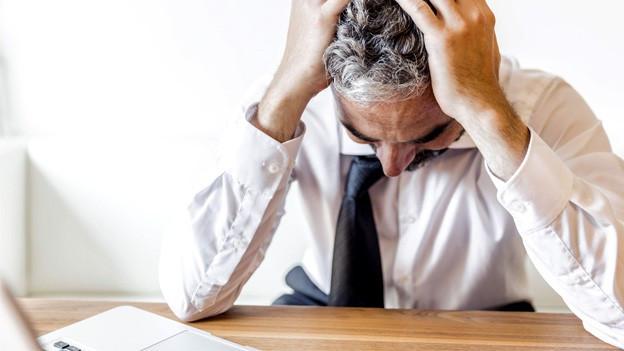 Mann vergräbt den Kopf in seinen Händen und sitzt vor einem Laptop.