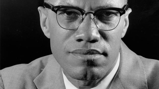 Porträtaufnahme von Malcolm X in schwarz-weiss mit Brille.