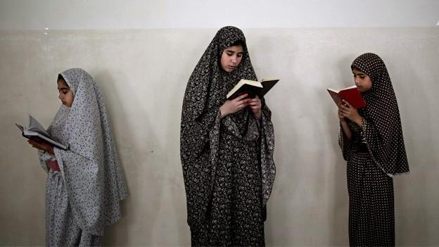 Drei Mädchen bekleidet mit einem Tschador lesen im Koran.