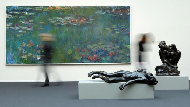 Zwei verschwommen fotografierte Menschen in einem Ausstellungssaal mit einem grossen Bild von Monet und zwei Skulpturen von Rodin.