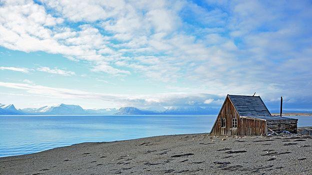 Eine Hütte steht einsam in der Landschaft.