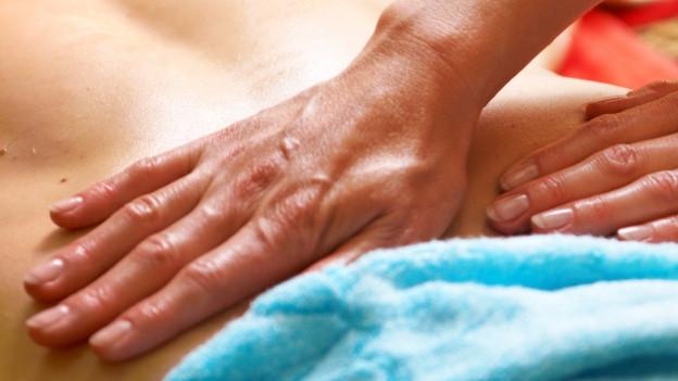 Rücken wird von zwei Händen massiert.