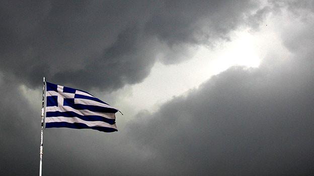 Griechische Flagge vor dunklen Wolken