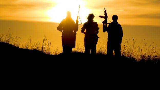Silhouetten dreier Männer mit Waffen