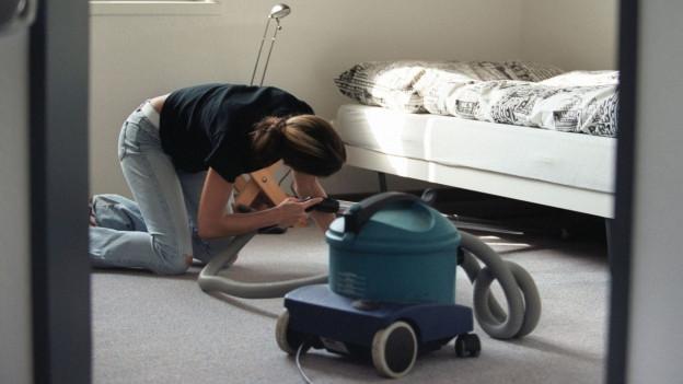 Symbolbild: Ein Frau kniet und saugt Staub unter einem Bett.