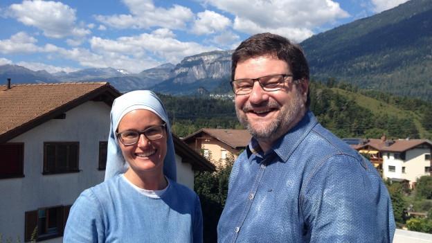 Eine Frau und ein Mann stehen auf einem Balkon. Im Hintergrund Häuser und eine grüne bergige Landschaft.