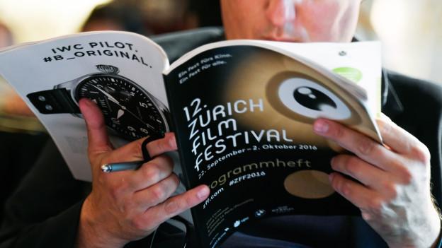 Mann liest Programmheft des 12. Zürich Film Festival.