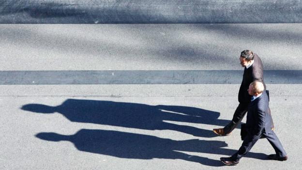 Zwei Gschäftmänner gehen im Gleichschritt und werfen dabe lange Schatten.